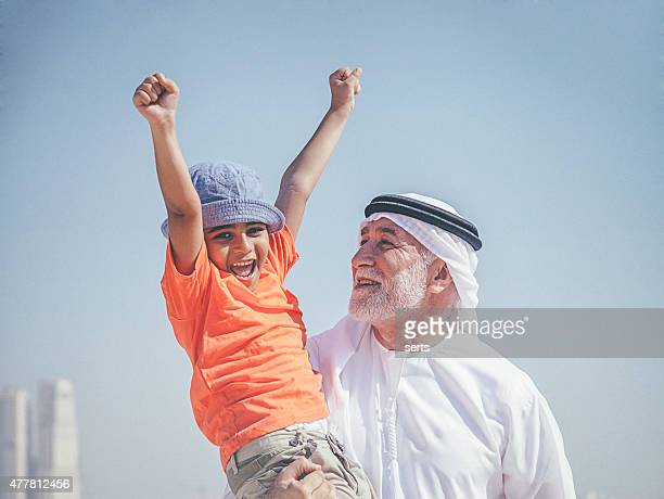 Arab grandfather and little boy having fun at beach