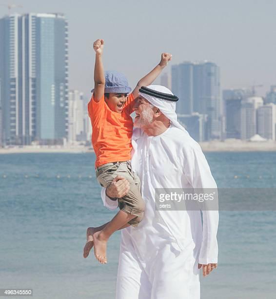 Arab grandfather and little boy having fun at beach