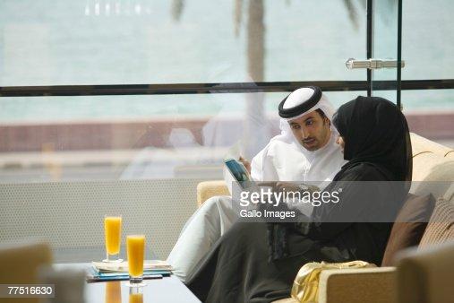 Arab Husband and Wife Reading Brochure. Dubai, United Arab Emirates