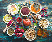 Arab ingredients for middle eastern food. Arabic cuisine ingredients on blue wooden background. Hummus, chickpea, lentils, rose buds, spices, pomegranate, pistachios. Halal food making. Top view