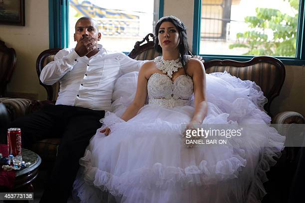 Arab Israeli Muslim groom Mahmoud Mansour and his Israeli bride Morel Malcha sit on a couch in Mahmoud's family home in the Jaffa district of Tel...