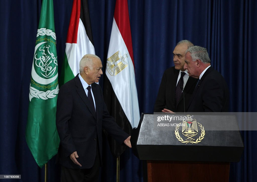 Arab League Secretary General Nabil al-Arabi (L) gestures towards Egypt's Foreign Minister Mohamed Kamal Amr (back-R) and Palestinian Foreign Minister Riyad al-Malki (front-R) during a press conference following their arrival in the West Bank city of Ramallah for a meeting with Palestinian president Mahmud Abbas on December 29, 2012.
