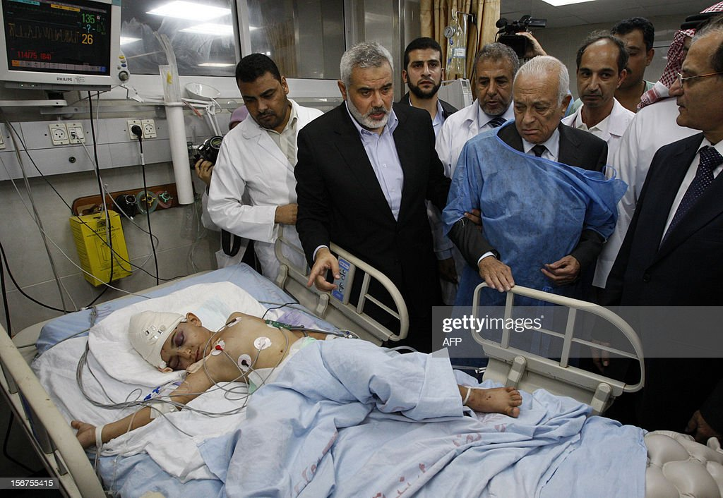 Arab League Secretary-General Nabil al-Arabi (C-R) and senior Hamas leader Ismail Haniya (3rd L) stand next to a Palestinian boy, who according to Palestinian medics was wounded in an Israeli air strike, at a hospital in Gaza City on November 20, 2012. A top delegation of Arab ministers led by al-Arabi began a solidarity mission in Gaza as an Israeli air offensive entered its seventh day. AFP PHOTO/POOL/Ahmed Zakot