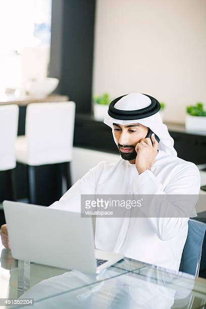 Arab Man Answering Client Calls at Home