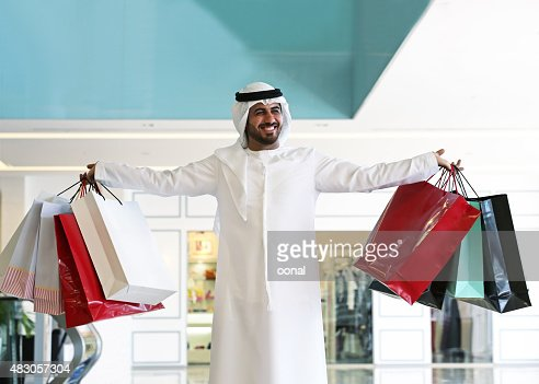 Arab man in shopping center with bags