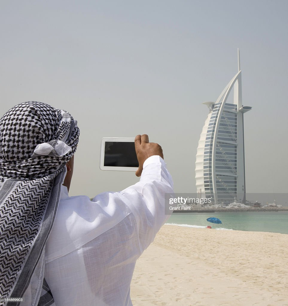 Arab man photographing building.