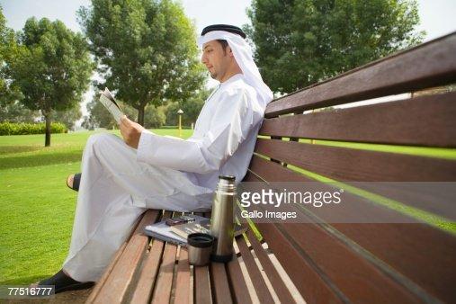 Arab Man Reading Newspaper on Park Bench. Dubai, United Arab Emirates