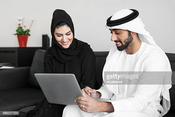 Arab Man Showing Something on Screen to His Wife