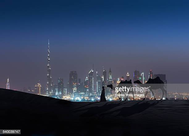 Arab man with camels at night  and modern city