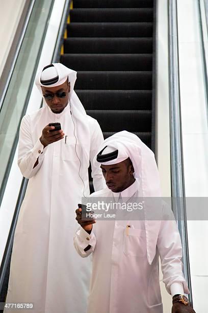 Arab men look at mobile phones on escalator