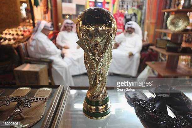 Arab men sit at a shoemaker's stall with a replica of the FIFA World Cup trophy in the Souq Waqif traditional market on October 24 2011 in Doha Qatar...