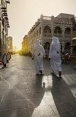 Arab men walking at Souk Waqif at sunset