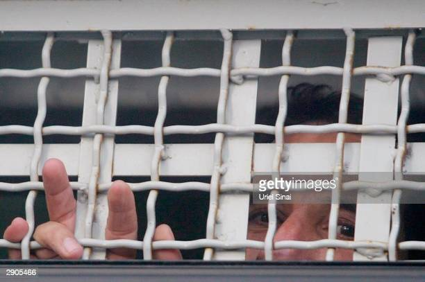Arab prisoners flash the Vsign for victory and peer through the barred window of an Israeli prison truck January 27 2004 in Tel Mond Israel...