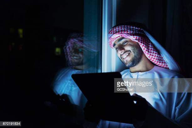 Arab reading a good book before going to bed on a digital tablet