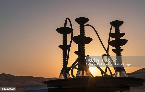Arab shishas (Water pipes) on a table in the desert at sunset, Abu Dhabi, UAE