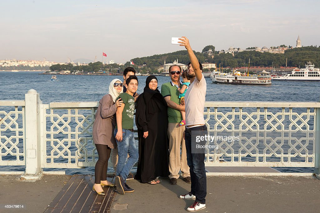 Arab tourists take a 'selfie' photograph on a smartphone against the backdrop of the Bosphorus straits in the Eminonu district of Istanbul, Turkey, on Sunday, Aug. 10, 2014. Investors said they will need to assess the next government's commitment to financial stability should Turkish Prime Minister Recep Tayyip Erdogan assume the presidency this month. Photographer: Kerem Uzel/Bloomberg via Getty Images