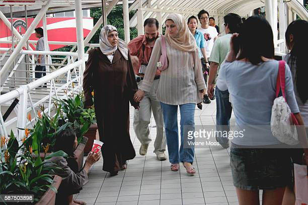 Arab visitors passing by a beggar in Bukit Bintang