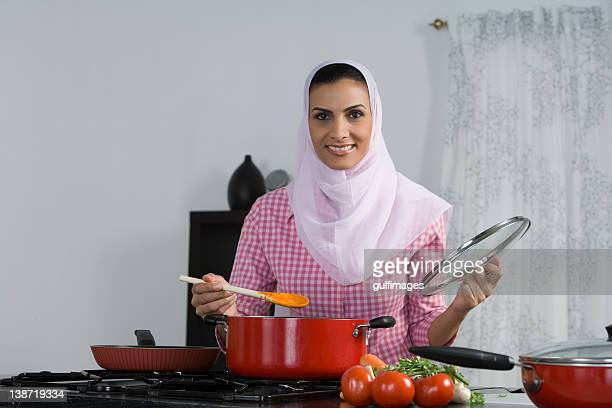 Arab woman cooking in the kitchen, smiling