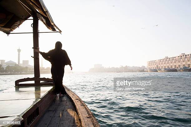 arab woman crossing Dubai Creek on a boat