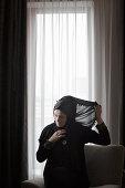 Arab woman wrapping her hijab.