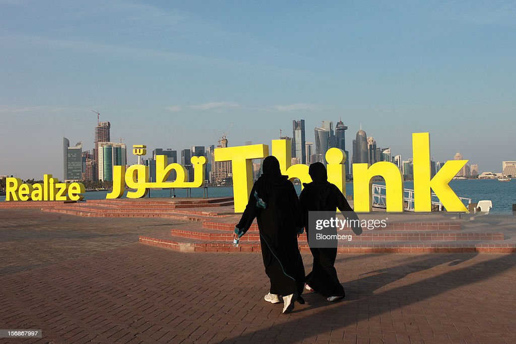 Arab women walk past artwork on the corniche waterside looking towards the city skyline in Doha, Qatar, on Thursday, Nov. 22, 2012. Qatar Telecom QSC, the country's biggest company by revenue, is seeking a syndicated loan for about $1 billion to refinance existing debt, according to a person with direct knowledge of the deal. Photographer: Gabriela Maj/Bloomberg via Getty Images
