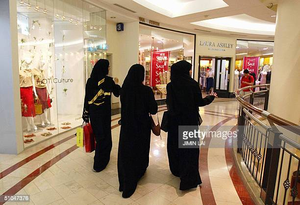Arab women walk past shopping outlets at a major commercial plaza in downtown Kuala Lumpur 06 July 2004 Tourists from the Middle East tired of being...