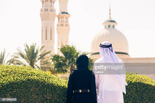 arabian couple standing in front of a mosque