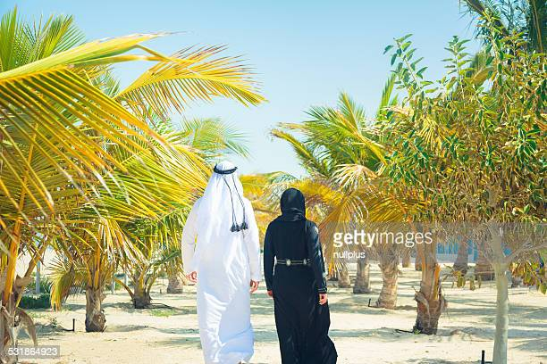 arabian couple walking among palm trees