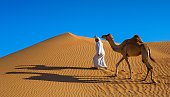 Local walking with his camel through the Arabian desert.