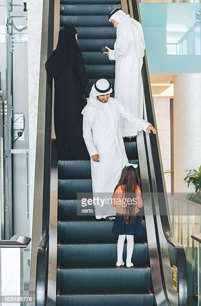 Arabian family on a shopping mall's escalator.