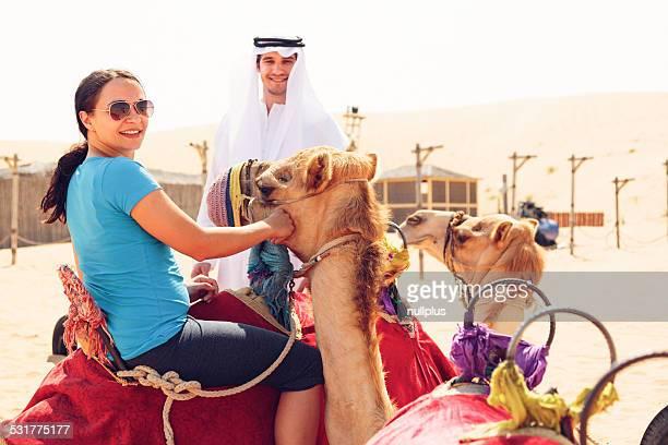 Arabische Mann und Touristen Kamelreiten