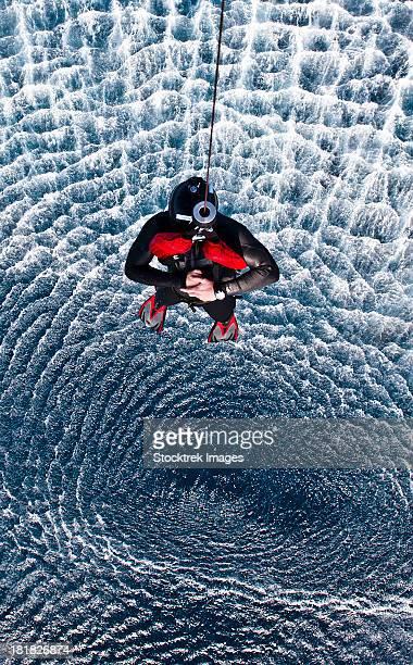 Arabian Sea, January 17, 2012 - An Explosive Ordnance Disposal Technician is hoisted to an MH-60S Sea Hawk helicopter.
