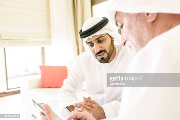 Arabic farther and son talking while using technology