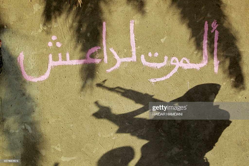 Arabic graffiti on the wall reads 'Death to Islamic State (IS)' in the Jurf al-Sakhr area, north of the Shiite shrine city of Karbala on October 26, 2014. Iraqi officials said that government forces backed by Shiite militias retook Jurf al-Sakhr, southwest of Baghdad, from Islamic State (IS) group militants on October 25.