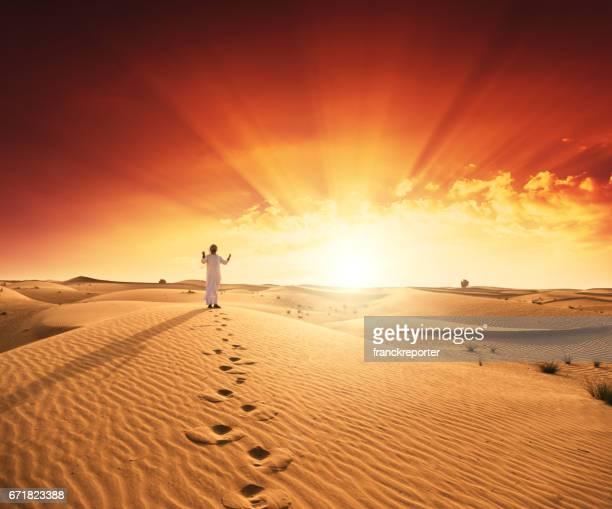 arabic man praying in the desert