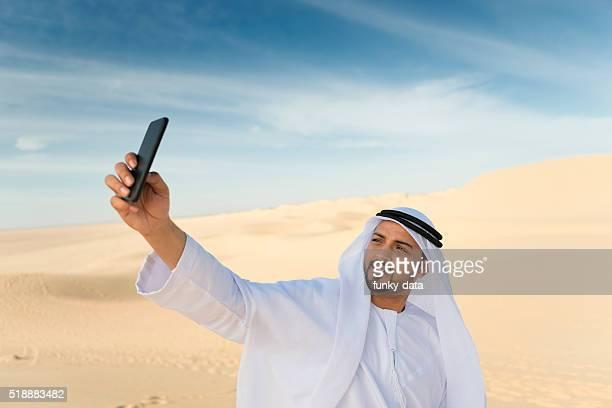 Arabic man taking a selfie in the desert