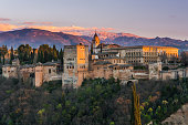 Arabic palace Alhambra in Granada,Spain at twilight with Sierra Nevada mountains in background