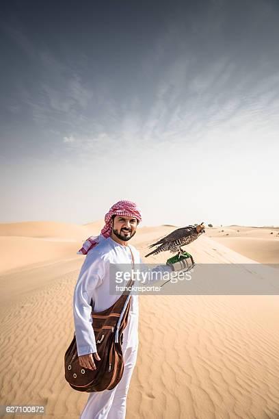 arabic sheik on the desert holding a falcon