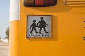 Arabic student crossing sign on yellow school bus. United Arab Emirates
