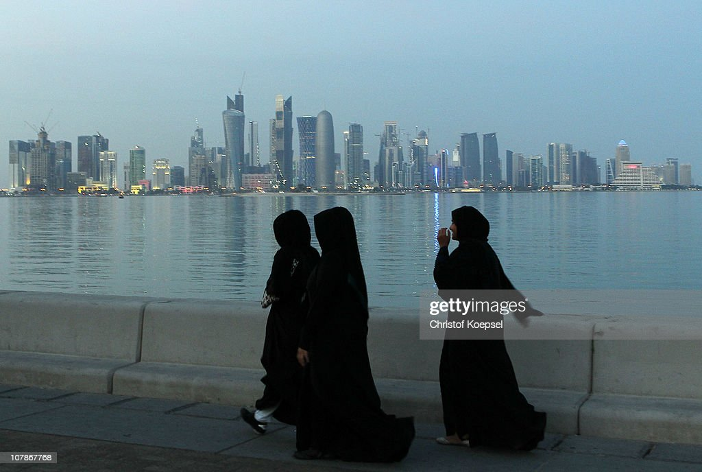 Arabic women walk alongside the skyline of the West Bay area in Doha on January 4 2011 in Doha Qatar The International Monetary Fund recently...