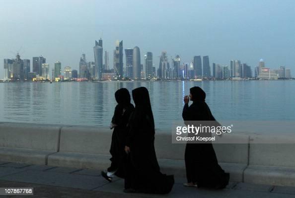 Arabic women walk alongside the skyline of the West Bay area in Doha on January 4 2011 in Doha Qatar The International Monetary Fund recently...