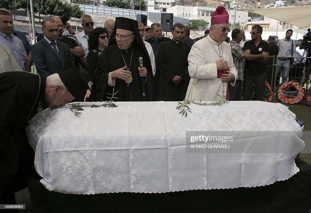 ArabIsraeli and Palestinian Christian Muslim and Druze mourners pray over the coffin of Samih alQasim a Palestinian Druze poet known across the Arab...