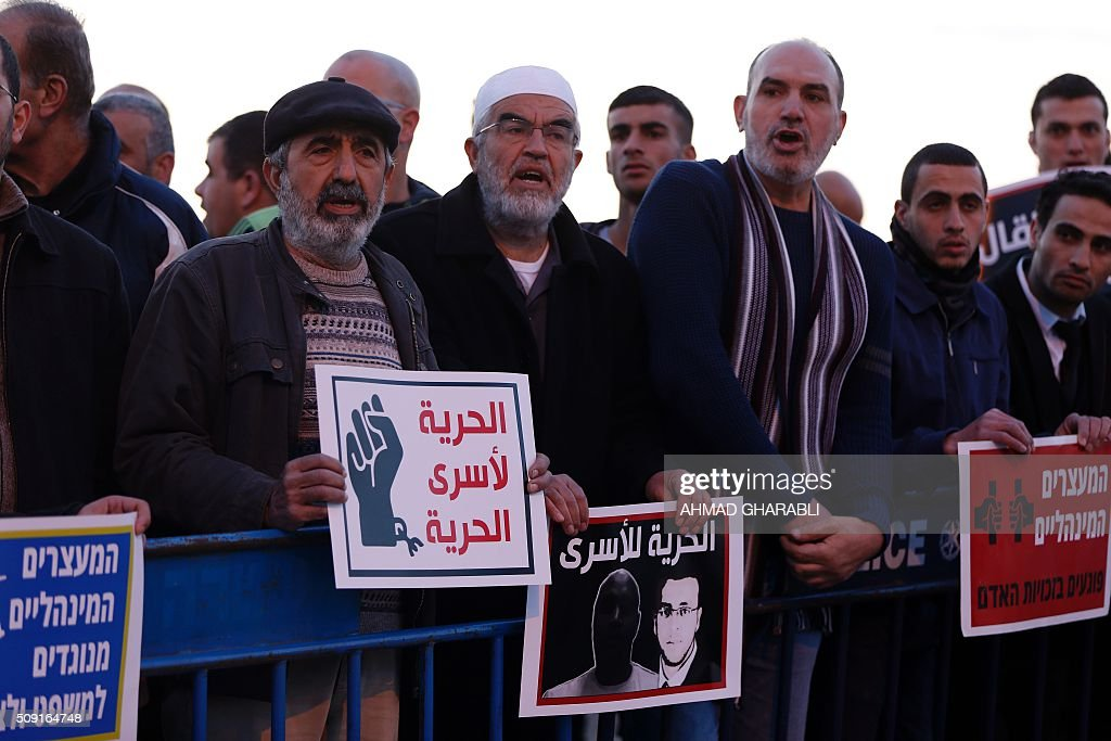 Arab-Israeli Sheikh Raed Salah (C), the leader of the radical northern wing of the Islamic Movement in Israel, stands among other Israeli Arabs in a protest calling for the release of Mohammed al-Qiq, a Palestinian prisoner on hunger strike, outside a hospital in the northern Israeli town of Afula on February 9, 2016. Ailing Palestinian journalist Mohammed al-Qiq will keep up his 10-week hunger strike despite Israel suspending a detention without trial order against him, his lawyer said. The 33-year-old television reporter, who still cannot leave hospital without permission, is 'determined to continue his fast until he is freed', Jawad Boulos told AFP. GHARABLI