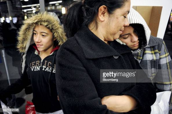 Araceli Romero center looks over at her daughter Damaris Romero as they wait for other family members to finish shopping at a Gap Inc outlet store in...