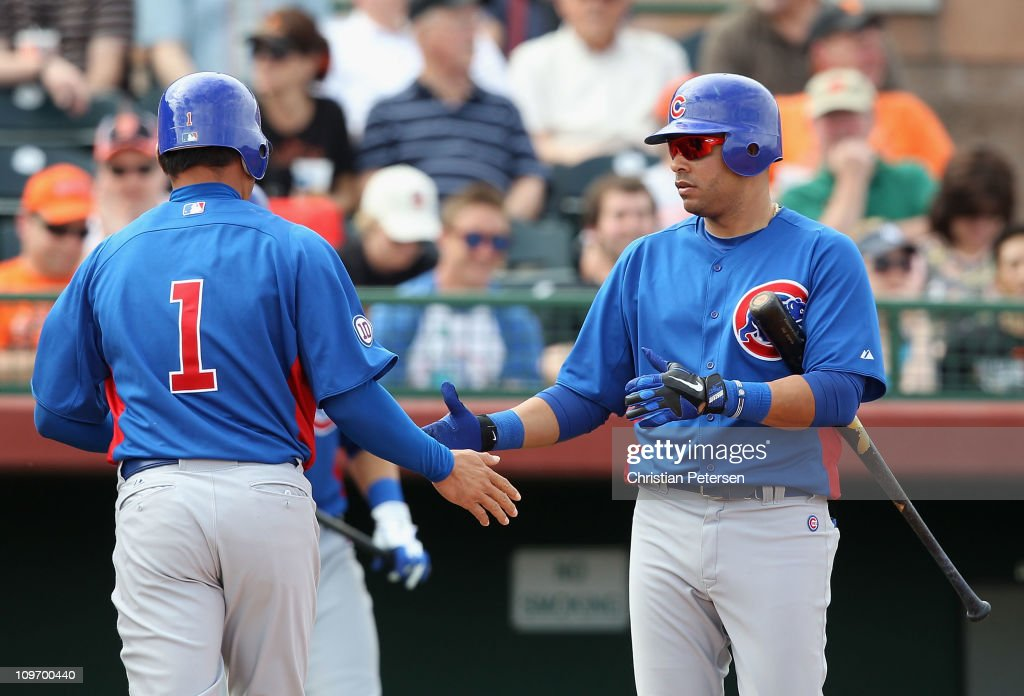 Aramis Ramirez of the Chicago Cubs highfives teammate Kosuke Fukudome after Fukudome scored a run against the San Francisco Giants during the sixth...