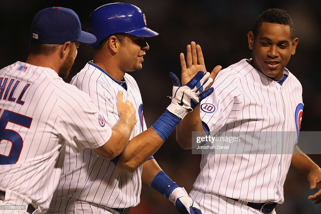 Aramis Ramirez of the Chicago Cubs is congratulated by teammates Koyie Hill and Carlos Marol after getting the gamewinning hit as a pinchhitter in...
