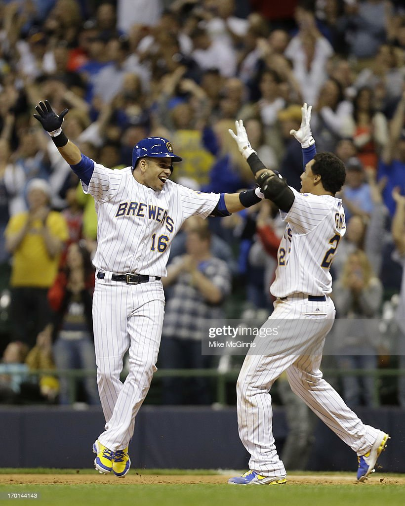 Aramis Ramirez of the Milwaukee Brewers celebrates with Carlos Gomez after hitting a walkoff single in the bottom of the ninth inning to put the...