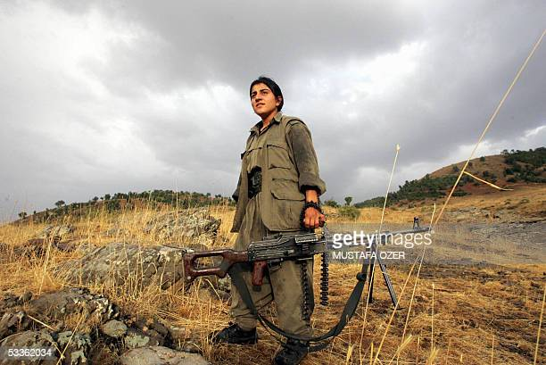 A PKK woman on her way to practice with a rifle loaded with life ammunition in a guerilla camp at Haqourki Mountain near Diana 11 August 2005 Prime...