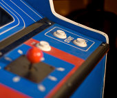 Control panel of a 1980s arcade machine with the start/player select buttons selectively focused.