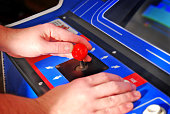 close up of a video arcade game joystick with hands of a gamer